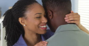 woman-holding-boyfriend-and-whispering-to-his-ear